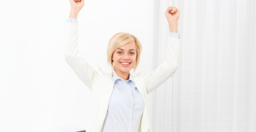 Business woman excited hold fist hands up raised arms sitting at modern office desk, surprised happy smile businesswoman success
